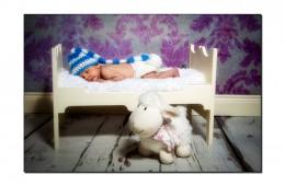 Newborn baby boy asleep on a wooden bed