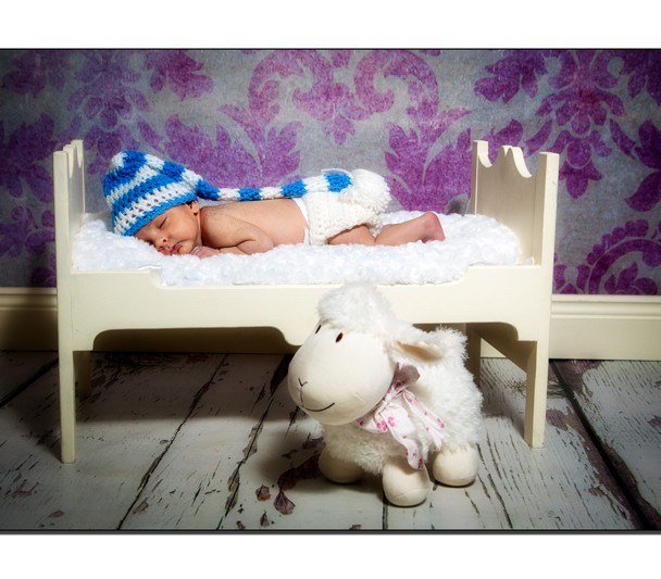 Newborn baby boy asleep on a wooden bed