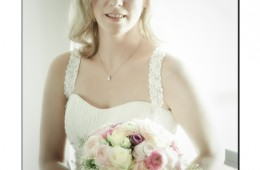 bride sitting in window with her floral bouquet