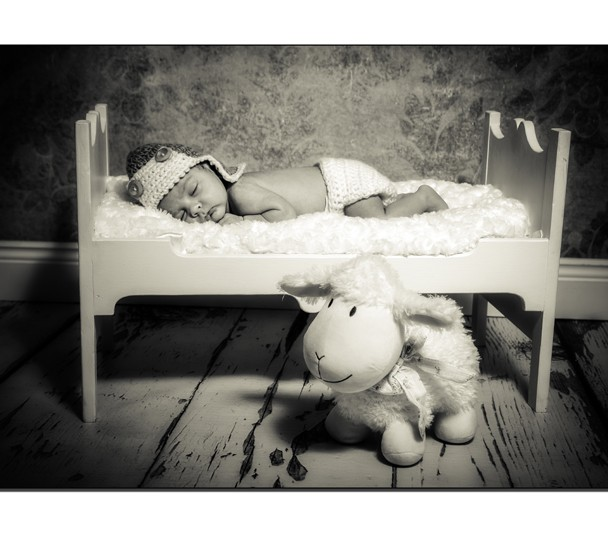 Baby boy with aviators hat asleep on a wooden bed
