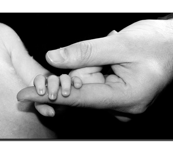 Newborn holding her mothers fingers