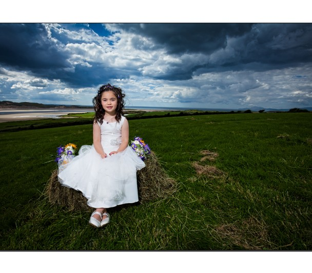Flower girl sits atop a bale of hay overlooking Erne Estuary Donegal Bay