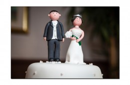 Model bride and groom atop cake