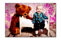 Baby boy sitting on a small wooden bed with teddy