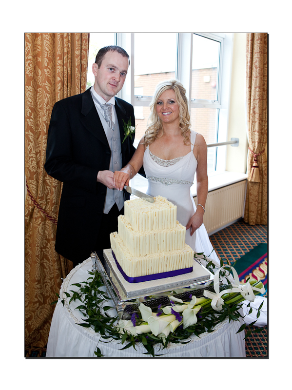 Bride and Groom cutting white chocolate cake