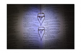 Rings casting a heart shadow over the bible