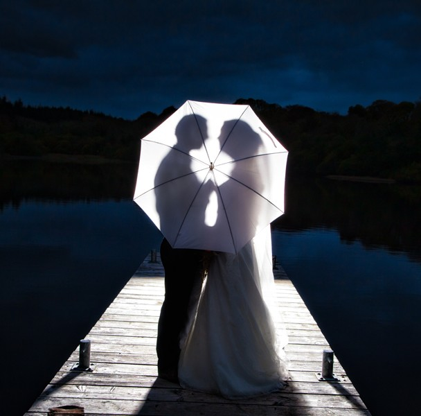 couple silhouetted kissing behind an umbrella