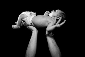 dad holding up newborn baby girl