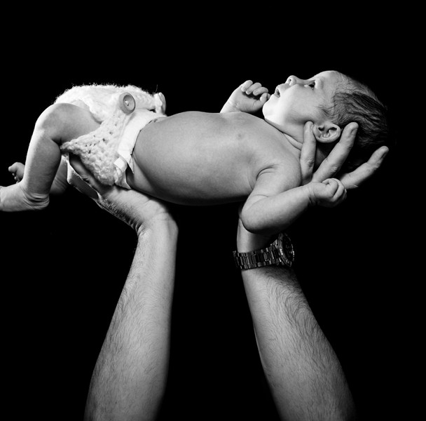 dad holding up newborn baby girl