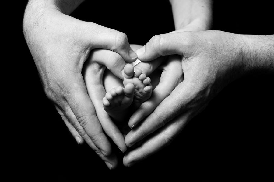 Newborn babies feet in parents hands
