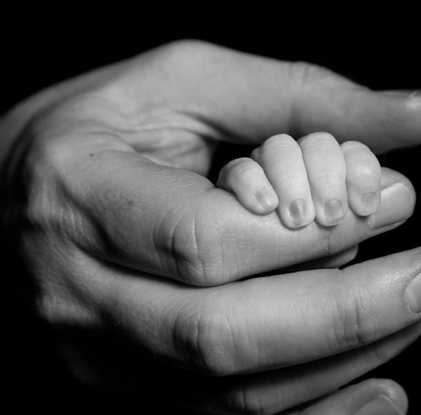 newborn baby holding dads finger