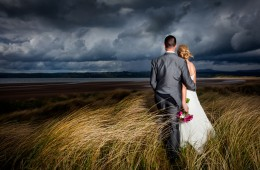 wedding photographer sligo couple on sand dunes looking over a beach