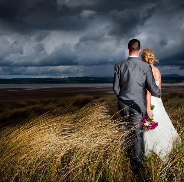 wedding photographer sligo couple on sand dunes looking over a beach