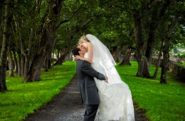 wedding photographers donegal bride and groom kiss in a tree lined lane