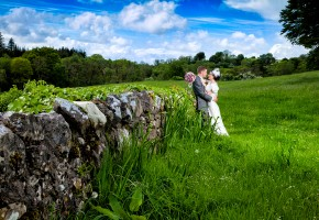 stunning bride and groom in a beautiful meadow leaning against an old stone wall for an amazing wedding photo