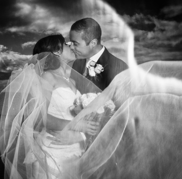 bride and groom kiss behind the wedding veil blowing in the wind