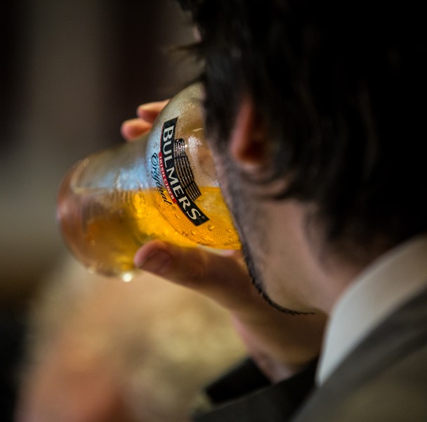 wedding guest drinking a pint of bulmers