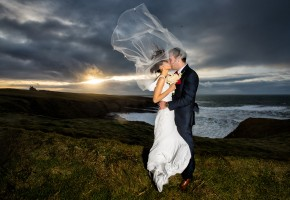 Donegal and Sligo Wedding Photographer bride and groom on the edge of donegal bay with a beautiful sunset behind them and the brides veil blowing straight up in the wind