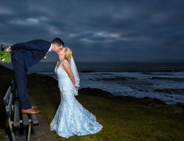 sligo wedding photography bride and groom kiss on a bench by the sea