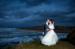 bride and groom kiss on cliff top at donegal bay