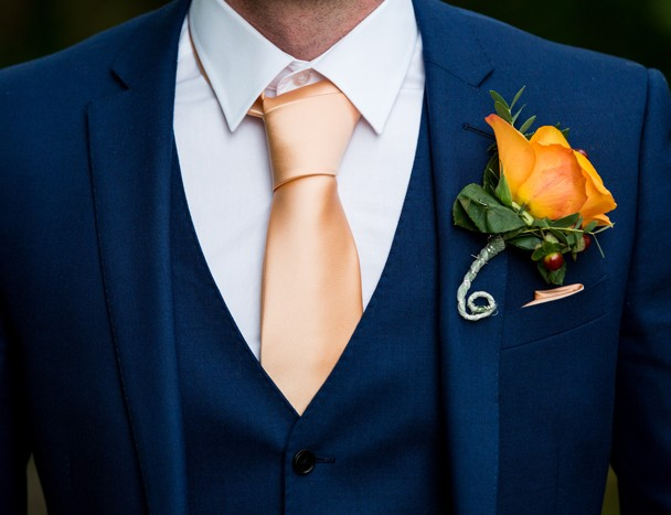 autumn colours for grooms wedding suit and flower