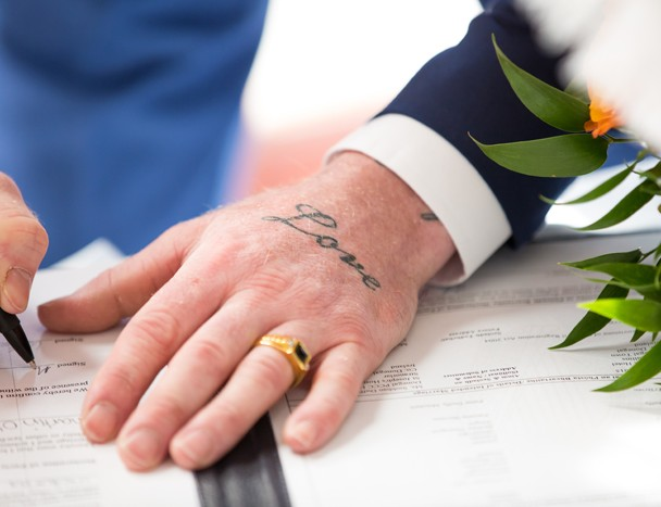groom with love tattoo on his hand signs the register