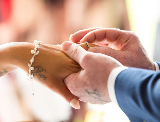 groom putting wedding ring on brides finger