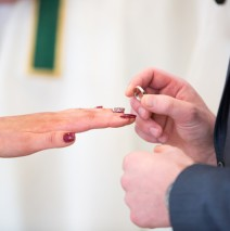 groom putting ring on brides finger