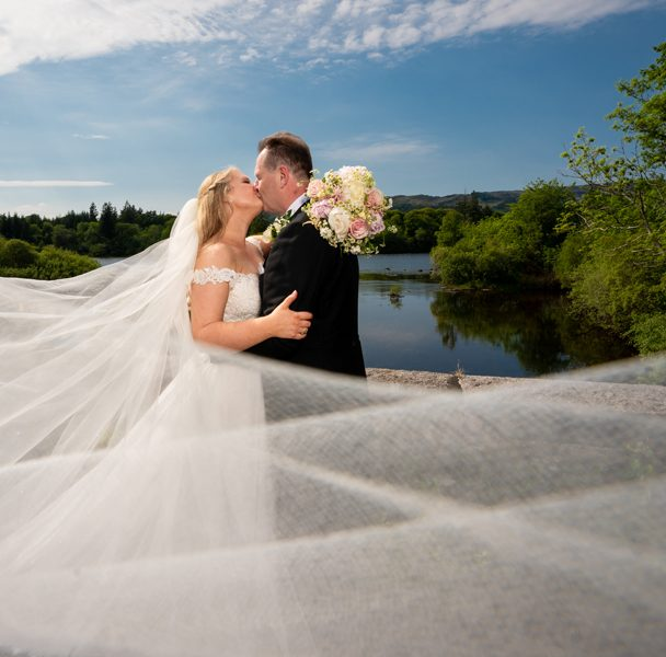bride and groom kiss on the shore of lough eske