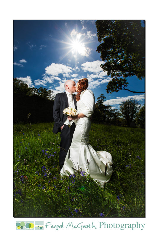 Hannah and Brian Clancy Wedding photo standing in a field of bluebells, meadow, bright sun, backlight wedding photo, kissing bride and groom