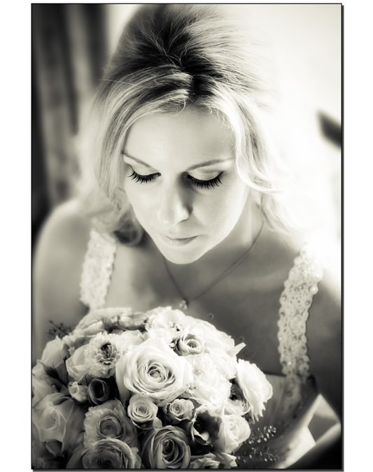 bride looking at bouquet black and white image