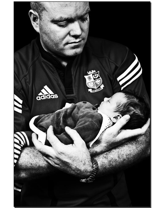 Father cradles newborn girl