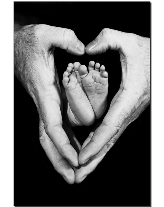 Fathers hands make a heart around his babys feet