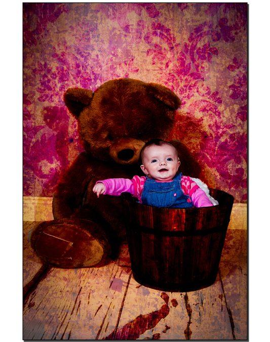 Baby girl in a planter pot with a big teddybear