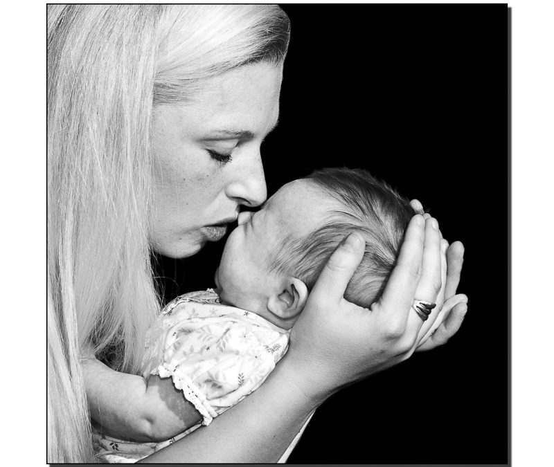 Mother kissing newborn baby girl