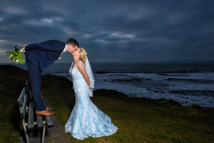 sligo wedding photography bride and groom kiss on a bench by the sea