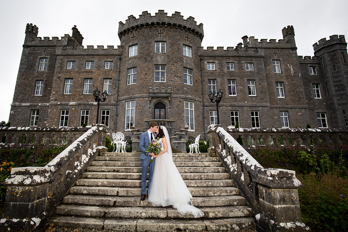 bride and groom on the steps of markree castle in sligo on their wedding day