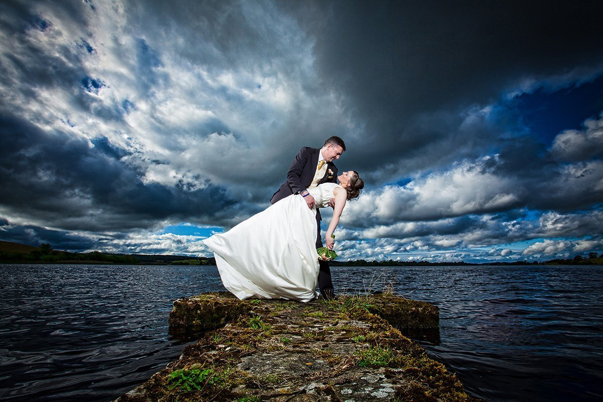 radisson bul hotel sligo wedding photo groom dips his bride in a stunning pose beside the water