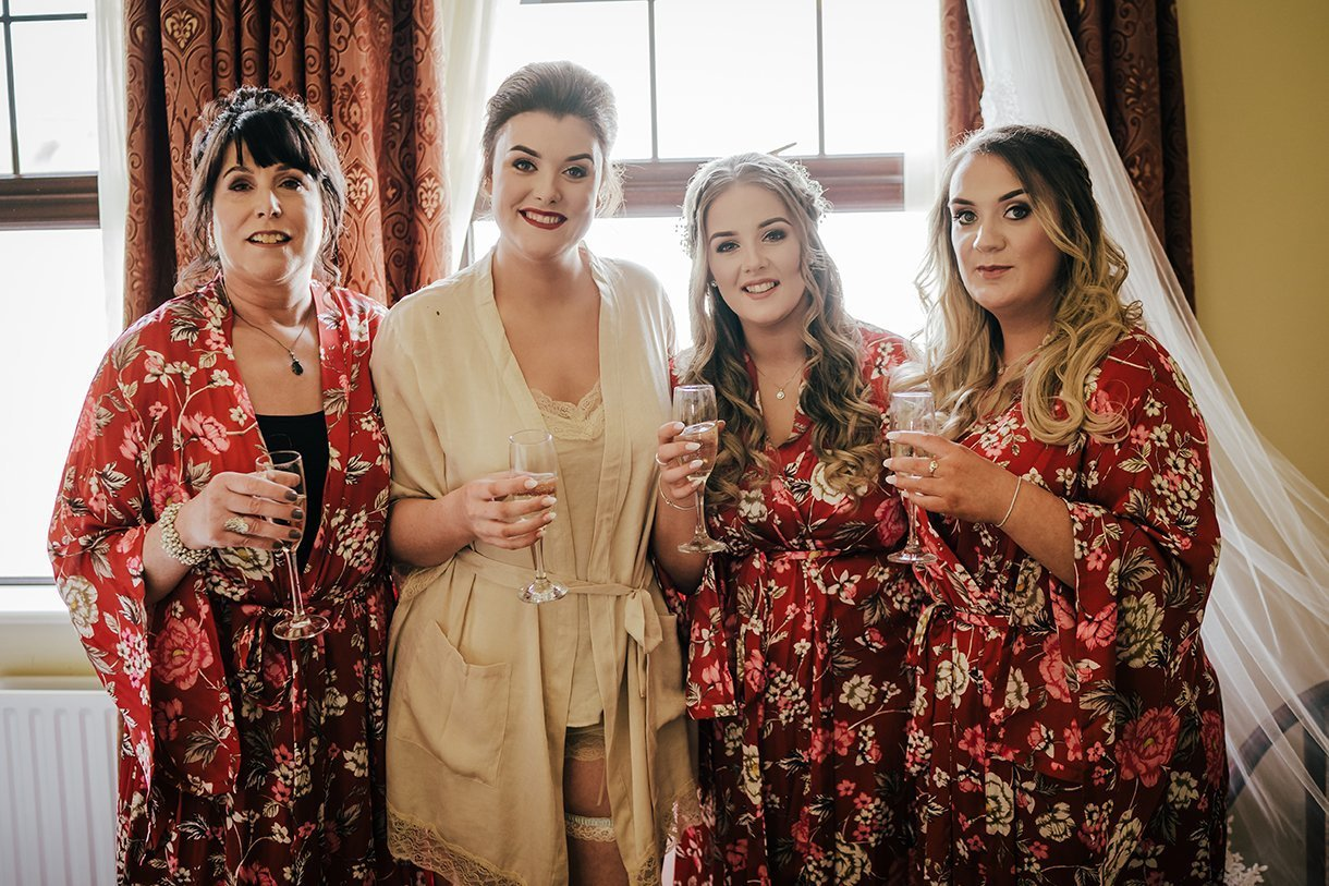 An Chuirt Hotel Gweedore Weddings bride and bridesmaids drink champagne