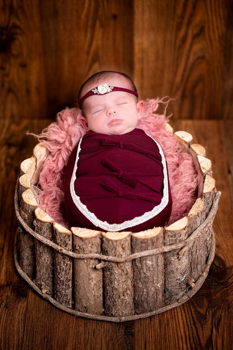 Sligo newborn photographer ireland newborn baby girl wrapped in a red wrap with matching headband in a rustic wooden bucket