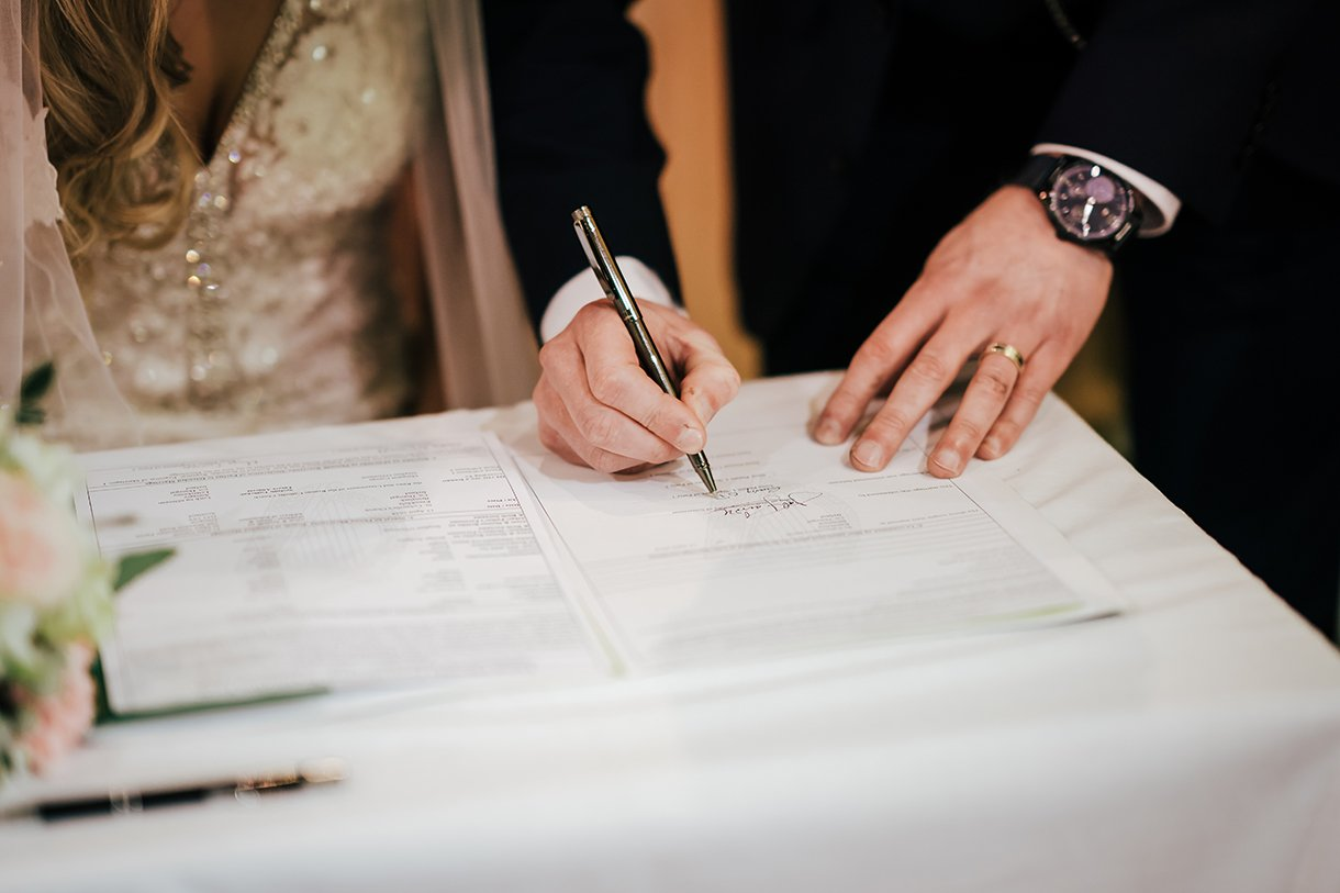 Waterfront Hotel Dungloe Wedding the groom signs the register