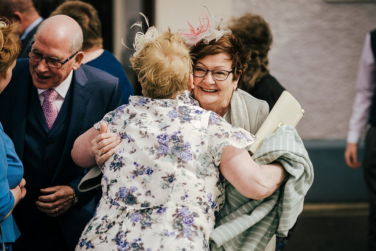 Waterfront Hotel Dungloe Wedding wedding guests hug outside the church