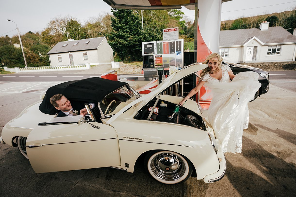 Waterfront Hotel Dungloe Wedding bride fills the wedding car with petrol while the groom waits inside the car