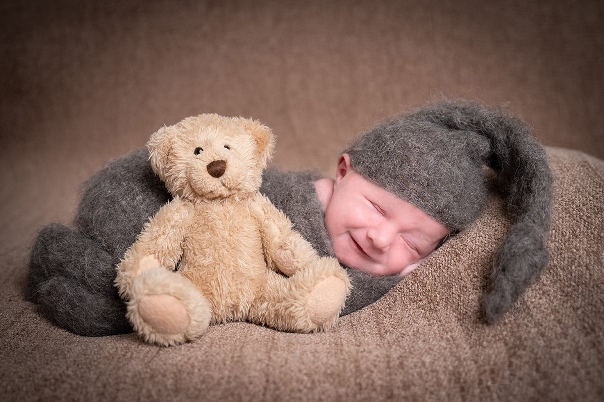 donegal and sligo newborn boy photographers smiling baby boy with a small teddy bear