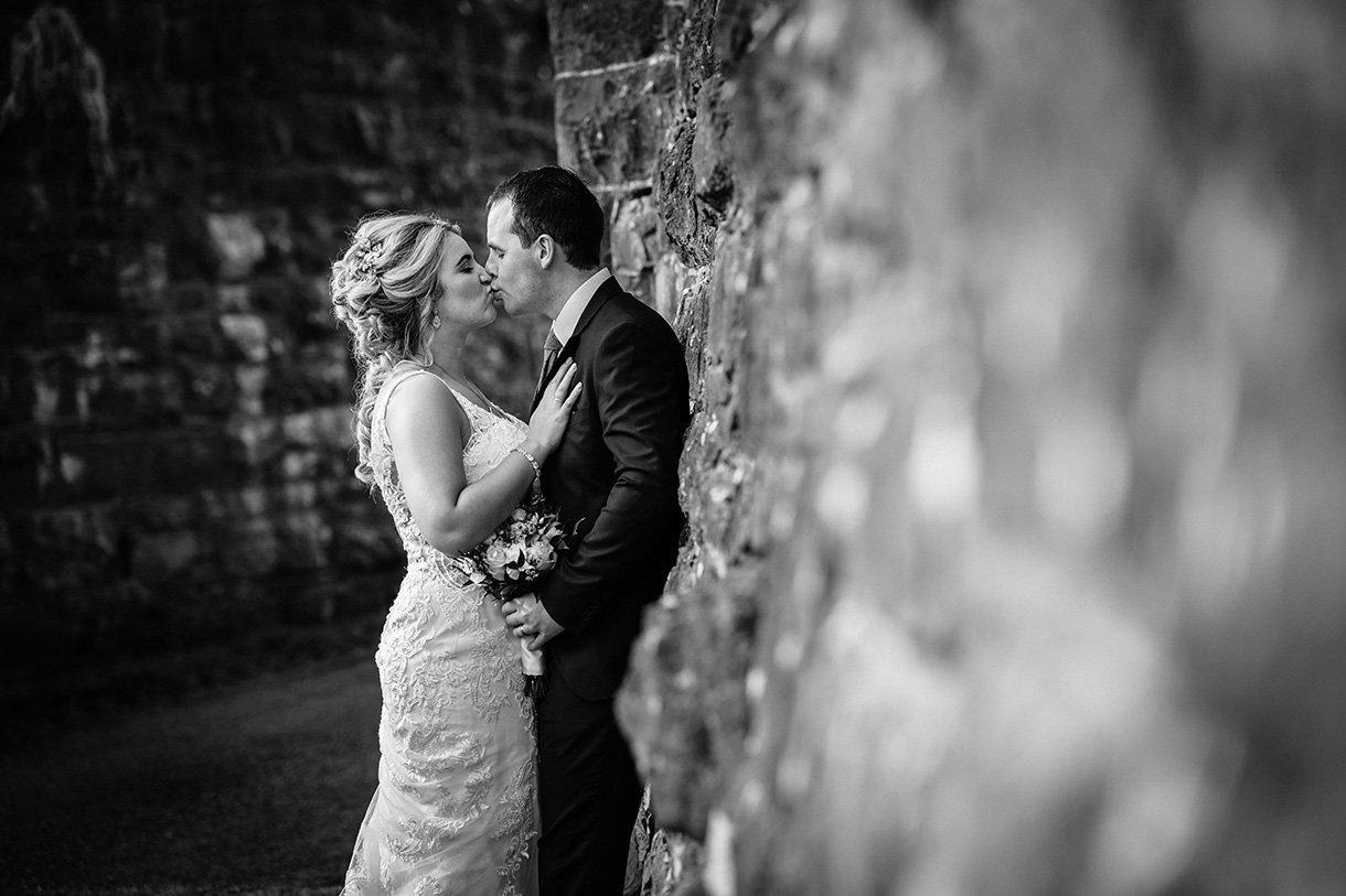Sandhouse Hotel Rossnowlagh Wedding bride and groom kiss along old stone wall