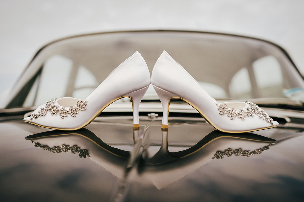 Sandhouse Hotel Rossnowlagh Wedding brides wedding shoes reflected in old vintage wedding car bonnet