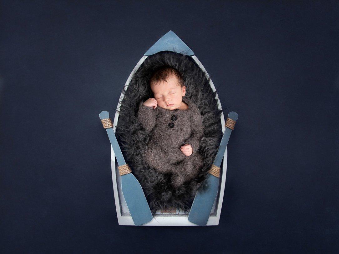 irish newborn photographer newborn boy asleep in a wooden boat