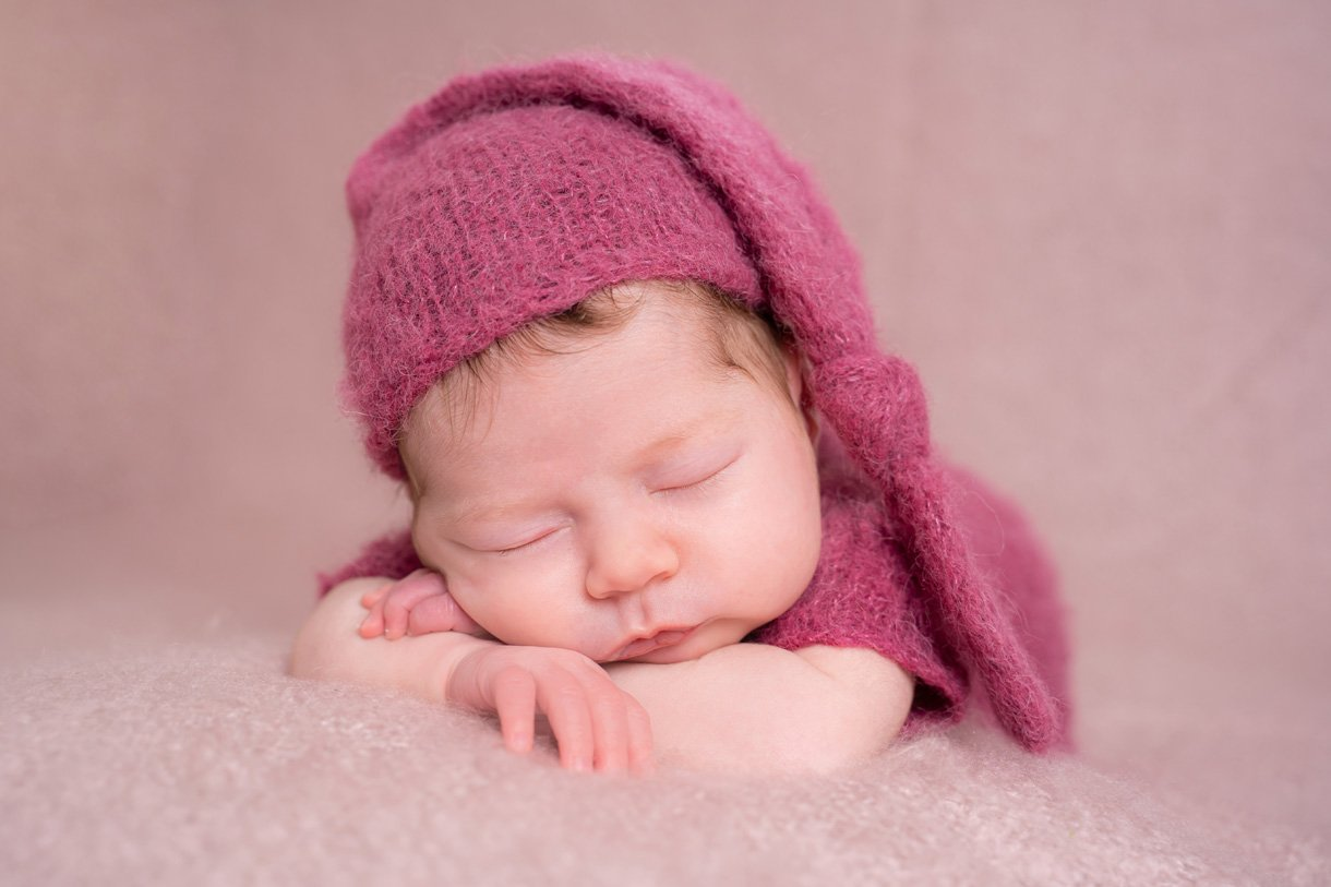 newborn baby girl in sleepy hat on a beanbag pose